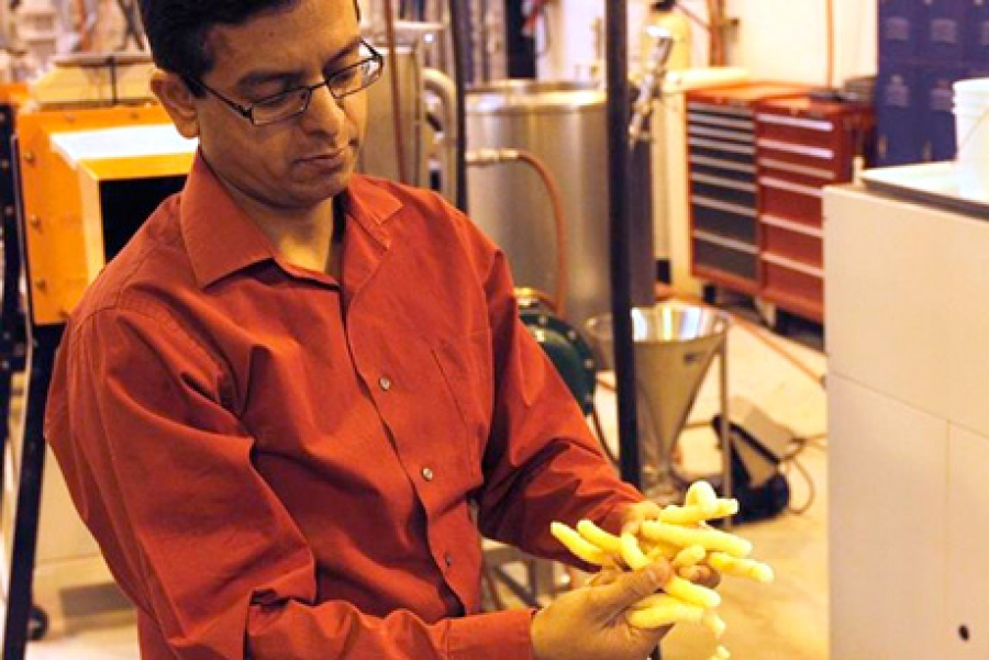 WSU professor Girish Ganjyal holds the snack puffs he and his students made with added carrot pomace. (Credit: Scott Weybright, WSU)
